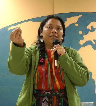 photo: Lolita Chavez, debout, micro à la main gauche, les doigts de sa main droite tenues ensemble pendant qu'elle s'exprime sur comment son peuple voit la vie. Derrière elle, une carte bleu du monde de la salle de conférence de l'Auberge L'Autre Jardin.