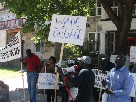 "A banner reads ""Wade Degage"" (""Out with Wade"") as protestors noisely chanted in front of the Senegalese Embassy in the Ottawa neighbourhood of Sandy Hill."