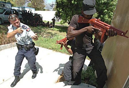 An RCMP officer trains a member of the Haitian National Police. Under the RCMP's watch, the HNP would kill thousands. During the same period, Coderre lauded the RCMP's efforts.
