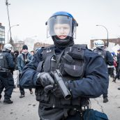 A Montreal Riot Police officer holding a rubber bullet hand gun at Montreal's 18th annual Protest against Police Brutality.