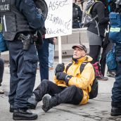 A older protester defiantly sits in fromt of Riot Police during Montreal's 18th annual Protest against Police Brutality.