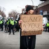 A protester holding a sign in front of Montreal Police.