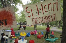 "Children play under a provocatively-worded sign, reading ""St. Henri disobeys"" (Sophie Blais)"