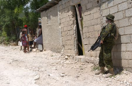 A Canadian soldier conducts a house search in 2004. Canadian Forces often provided backup for HNP raids, which killed thousands of political dissidents.